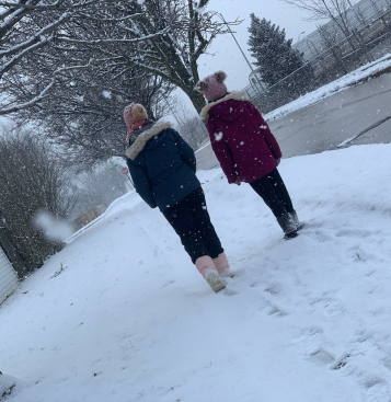 My sister and I walking in the snow. I'm in the blue coat and I'm wearing a finished hat like the one I'm making my mom!
